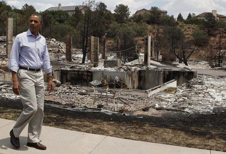 U.S. President Barack Obama walks around fire damaged homes