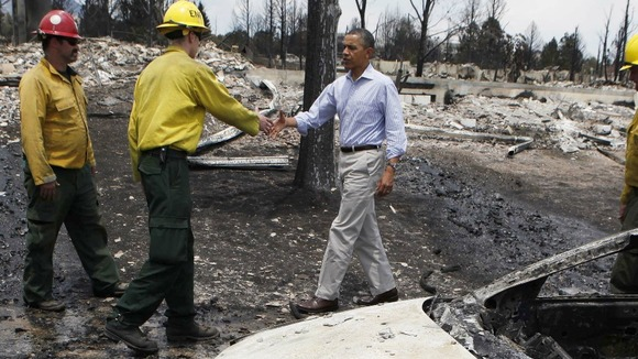 President Barack Obama looks over fire damaged homes in the Mountain Shadow